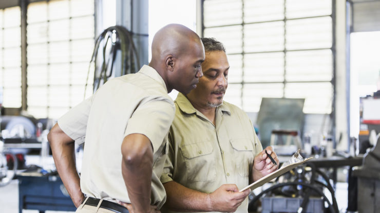 Two multi-ethnic men working for a trucking company, standing in a garage, looking down at a clipboard. The African-American man is in his 30s. His coworker or manager is a mature Hispanic man is in his 40s.